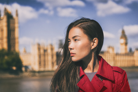 Asian beauty woman fashion at London city, Westminster, Big Ben in the background. Fashion model wearing red lipstick makeup with serious face. Autumn travel lifestyle. Stock Photo