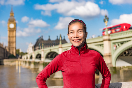 London lifestyle woman running near Big Ben. Female runner jogging training in city with red double decker bus. Fitness girl smiling happy on Westminster Bridge, London, England, United Kingdom. Stock Photo