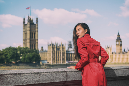 London fashion week Asian model woman at Westminster parliament, iconic british landmark Big Ben city background. Autumn trend lady wearing red trench coat rain outerwear. Europe travel lifestyle. Stock Photo