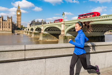 London city lifestyle sport woman running near Big Ben. Asian girl runner jogging training at Westminster bridgeg with red double decker bus. Fitness athlete happy in London, England, United Kingdom.