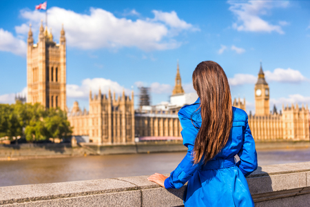 London Westminster Europe city travel urban tourist woman looking at parliament and Thames river, famous tourism attraction landmark. Autumn season people lifestyle. Banco de Imagens - 94592643