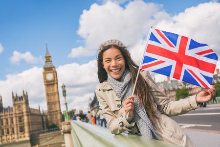 London travel tourist woman showing Union flag Great Britain british UK flag. Asian girl at Big Ben on Westminster bridge on Europe holidays holding icon at iconic landmark. Archivio Fotografico