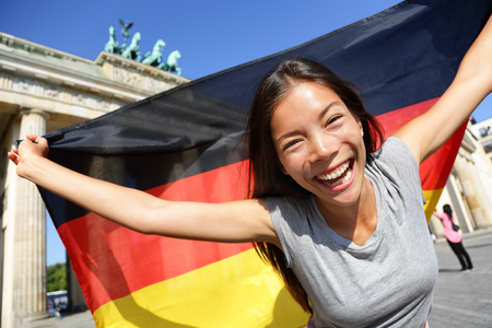 Cheerful young woman waving German flag in front of Brandenburg Gate. Portrait of happy female enjoying her vacation in Berlin. Beautiful woman is celebrating her holidays.