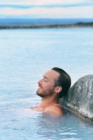 Wellness spa handsome man relaxing enjoying natural geothermal hot spring in outdoor Iceland nature. Reykjavik tourist nordic travel. 스톡 콘텐츠