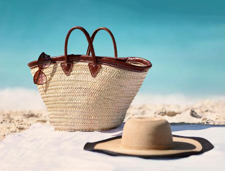 Sun vacation beach winter travel holiday background- Beach bag, fashion hat and sunglasses for Caribbean relaxation. . Copy space on blue ocean. Fashion stylish luxury accessories. Stock Photo - 94857359