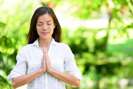 Attractive young woman meditating in park. Beautiful woman in casuals is standing with hands clasped. Young female with eyes closed practicing yoga in nature. Stock Photo