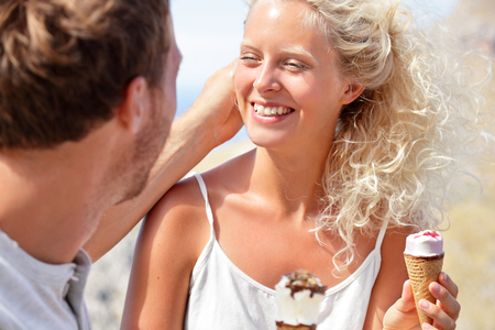 Cute couple eating ice cream cones together as summer treat. Young man in love taking care of his girlfriend touching her hair. Blonde woman laughing enjoying picnic in park.