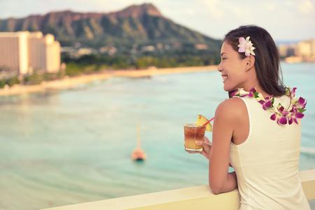 Hawaii vacation summer travel- Mai Tai and aloha spirit. Asian woman relaxing drinking Hawaiian cocktail drink Mai Tai, at sunset view of Waikiki beach in Honolulu, Oahu, USA travel. Stock Photo