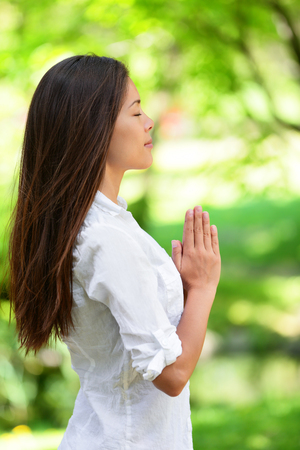 Young woman with hands clasped meditating in park. Side view of beautiful woman in casuals. Attractive female with eyes closed practicing yoga in nature. Фото со стока