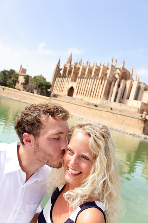 Couple in love kissing for photo selfie in Palma de Mallorca, Spain. Spanish cruise travel destination. Happy young lovers in summer vacation holidays.