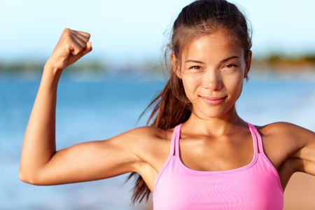 Confident sporty woman flexing muscles on beach. Beautiful young is wearing pink sports bra. Female is showing her strength and healthy lifestyle on sunny day.