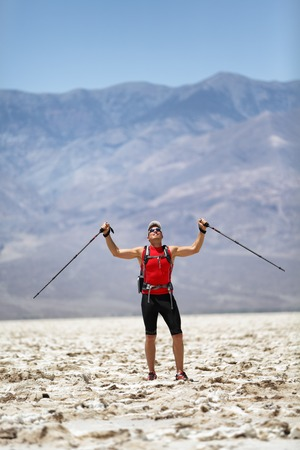 Hiker holding poles Cheering of Success against mountain. Full length of man in sports clothing on ultra running trail trek. Successful male is enjoying his vacation in Death Valley, USA travel.