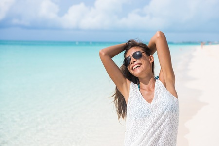Summer beach vacation relaxation - Happy girl enjoying sun relaxing wearing sunglasses and beachwear feeling free. Asian woman casual lifestyle.