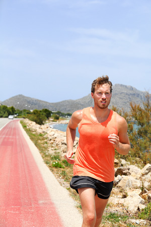 Exercise outdoor fitness man jogging on street training cardio outside in summer heat sweating. Sport athlete running in tank top sports clothes. Stock Photo