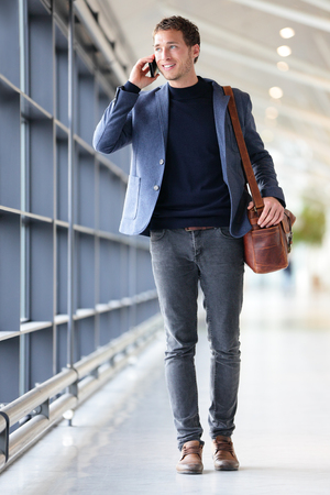 Urban business man talking on smart phone traveling walking inside in airport. Casual young businessman wearing suit jacket and shoulder bag. Handsome male model in his 20s. Foto de archivo