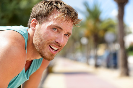 Sweating fitness man tired exausted of running in sun heat dehydrated with sweat dripping from face. Sunstroke athlete jogger jogging outside in city. Active sport lifestyle.