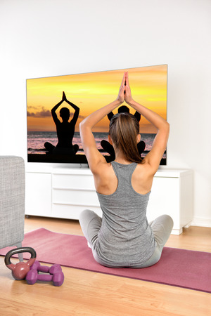 Home workout - woman exercising watching tv show on flat screen fitness program yoga exercising in living room. Yoga girl doing meditation exercise at home. Imagens
