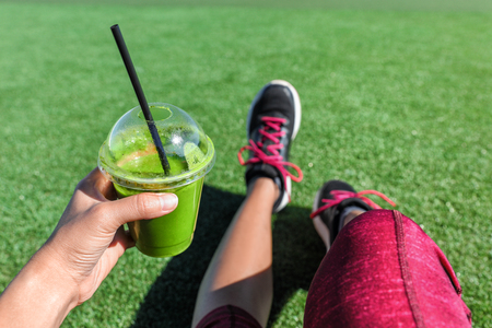 Green smoothie detox fitness girl drinking plastic cup take-out morning breakfast juice during run in summer park. Healthy lifestyle sport person POV of hand holding drink with running shoes selfie. Stock Photo