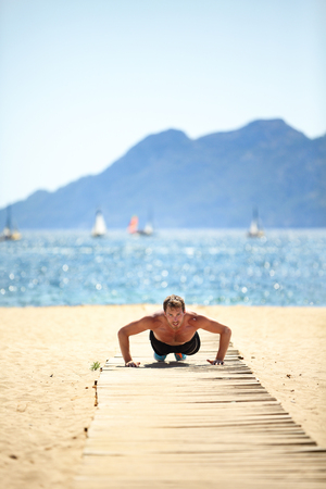 Sport beach fitness man doing push-ups. Handsome athlete training push up topless outside in summer sun. Fit male fitness model doing exercise outdoors. Healthy lifestyle concept. Active lifestyle. Stock Photo
