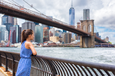 New York city NYC summer travel tourist woman enjoying view of Manhattan skyline from Brooklyn park living a happy lifestyle walking during USA vacation. Female Asian tourist in her 20s.
