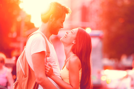 Couple in love laughing hugging looking at each other in sunset. People falling in love, happiness fun. Interracial young couple embrace on date. Caucasian man Asian woman on city street lifestyle. Stock Photo
