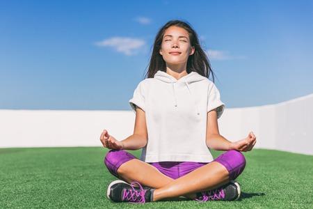 朝の瞑想をしているヨガの女の子。ウェルネスと健康。夏のアクティブなライフスタイル。公園の草の上で外で瞑想するアジアの女性。