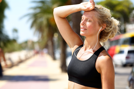Runner girl tired feeling exhausted from jogging outside in summer heat -sun stroke headache or dehydration during difficult training outdoors. Blonde fitness woman model touching forehead. Stock Photo