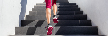 Hiit workout cardio running up the stairs training. Staircase climbing run woman going run up steps panorama banner. Runner athlete doing cardio sport workout. Activewear leggings and shoes. Stock Photo