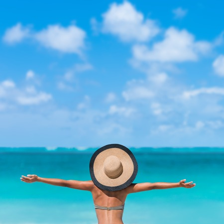 Beach summer holidays woman in happy freedom concept with arms up in happiness. Tourist vacation girl wearing fashion floppy sun hat carefree with copy space on blue sky.