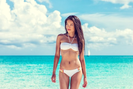 Sexy asian beach model woman beauty showing off toned abs and slim bikini body on tropical caribbean travel vacation. Girl with tanned skin and white fashion swimsuit. Stockfoto