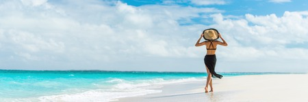 Luxury travel summer beach vacation woman walking in black beachwear skirt and hat on paradise white sand Caribbean beach. Lady tourist on Caribbean holiday vacation resort. Banner panorama landscape. Stock Photo