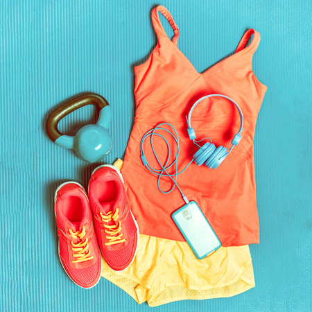 Gym outfit - workout fitness sportswear clothes and smartphone top view. Kettlebell weight, headphones for music, running shoes, shorts and sports top.