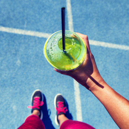 Green smoothie woman drinking plastic cup breakfast meal takeaway to go after morning run on blue tracks. Healthy lifestyle sporty person pov of hand holding glass with running shoes feet selfie.