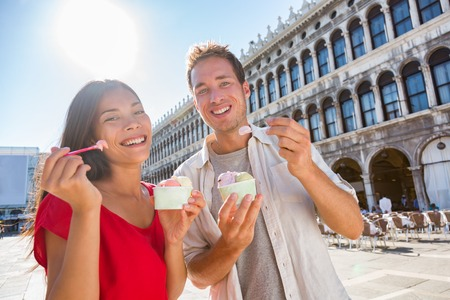 Happy couple tourists eating gelato ice cream on San Marco Square in Venice, Italy, Multiracial Asian woman Caucasian man on summer travel vacation eating italian food. Stock Photo