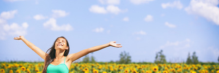 Summer girl happy in sunflower flower field for spring. Cheerful multiracial Asian Caucasian young woman joyful with arms raised up. Panoramic landscape banner.