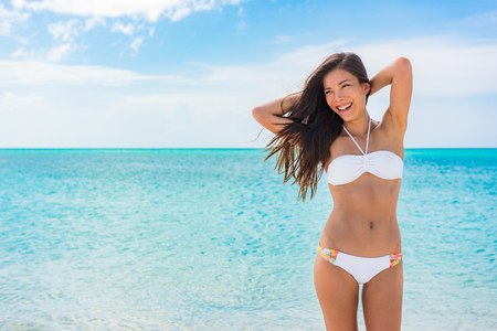 Toned abs sexy slim stomach bikini body woman on beach vacation background for weight loss and fat treatment concept. Happy Asian girl swimsuit model feeling good showing off waist and arms up.