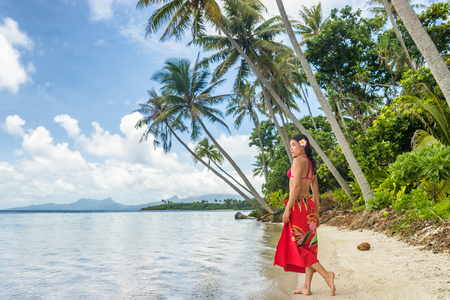 Tahiti luxe voyage plage vacances femme marchant en jupe polynésienne beachwear sur une île paradisiaque idyllique en Polynésie française. Vêtements traditionnels rouges, bikini et fille de fleur.