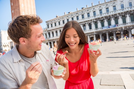 Happy couple laughing eating ice cream on vacation travel in Venice, Italy. Smiling happy young couple in love having fun eating italian gelato food on San Marco Square, Venice, Italy holidays. Imagens