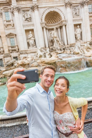 Rome couple at Trevi Fountain Italy vacation. Happy young travel tourists traveling in Europe taking photo with phone camera. Man and Asian woman happy together.