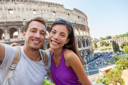 Travel selfie couple taking photo with phone at colosseum famous landmark in Rome city. Europe Italy summer vacation young people smiling. Backpacking road trip. Banco de Imagens - 95429732