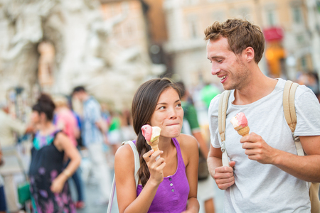 Ice cream summer fun couple eating gelato in Rome on Piazza Navona. Happy people having fun eating ice cream on vacation travel in Italy, Europe. Young funny girl licking lips of italian food outdoor. Stock Photo