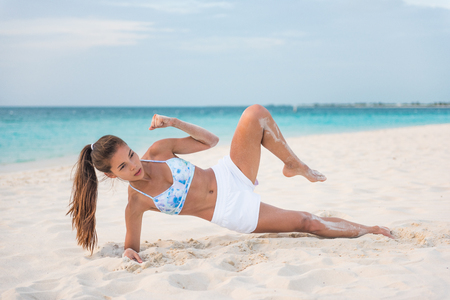 How to do a Side Plank Crunch fitness instruction demonstration physical trainer on beach training obliques stomach muscles doing core body training. Fit girl exercising doing abs exercise. Standard-Bild - 95429690