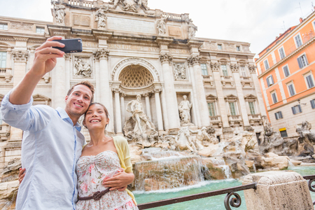 Rome travel tourists couple at Trevi Fountain in Rome, Italy vacation. Happy young romantic couple traveling in Europe taking self-portrait with smartphone camera. Man and woman happy together
