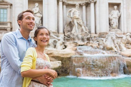 Rome travel tourists couple at Trevi Fountain in Rome, Italy vacation. Happy young romantic interracial couple traveling in Europe. Man and Asian woman embracing together. Stock Photo