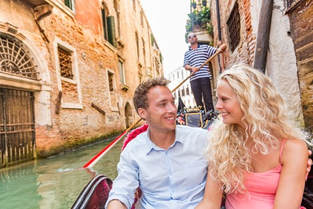 Honeymoon couple in Venice gondola romantic cruise happy tourists on summer luxury travel vacation. Young people in love smiling in boat ride in Venetian canals of old city, Italy. Europe holiday. Banque d'images