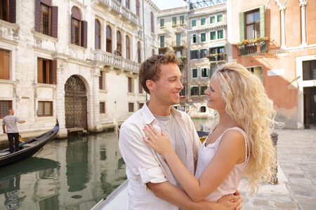 Romantic honeymoon couple in Venice city street near Grand Canal in love hugging in summer Italy travel. Blonde woman and man looking at each other on Europe vacation holidays. . Banque d'images
