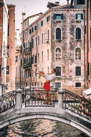 Romantic couple dancing jumping in love on Venitian canal bridge on honeymoon travel in Venice. Lovers getaway romance, caucasian man and woman embracing. Summer holiday city streets, Italy.