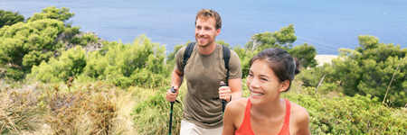Happy hiking young people climbing mountain with walking sticks. Interracial hikers couple enjoying summer holidays in nature travel vacation. Panorama banner.