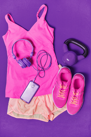 Activewear fitness clothes outfit - cute pink fashion matching clothing for girl training with weights and phone headphones to listen to music during workout at gym on purple exercise mat background.