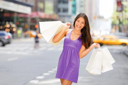 Shopper woman holding shopping bag walking in New York City having fun outside in NYC summer. Asian girl in purple pantone color fashion dress buying bag. Clothing purchase customer.